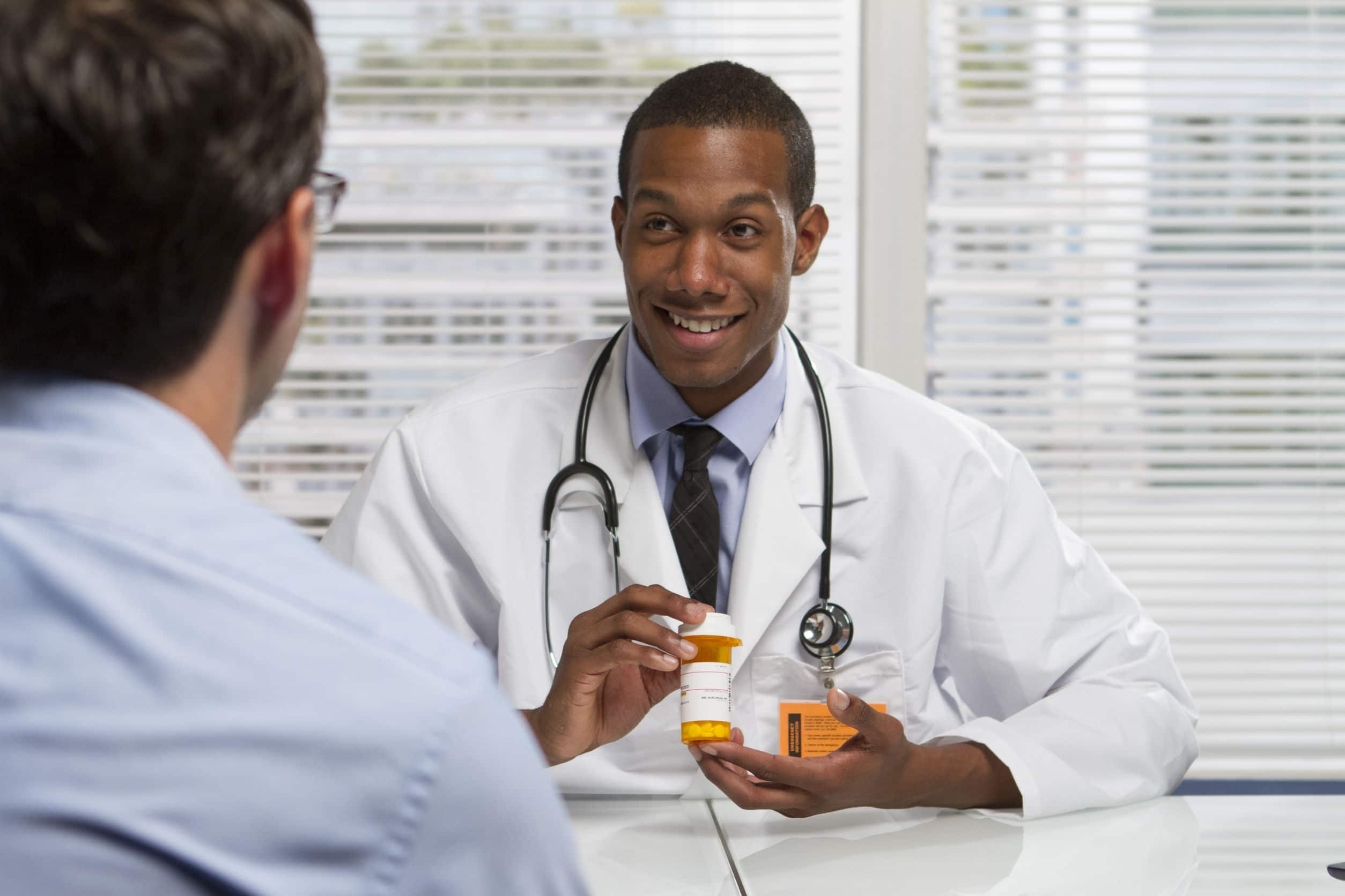22665451 – young black doctor showing patient prescription, horizontal